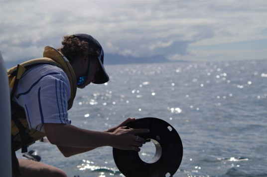 Rose Fleming checking water clarity with Secchi disk (photo credit: Chloe Cargill)